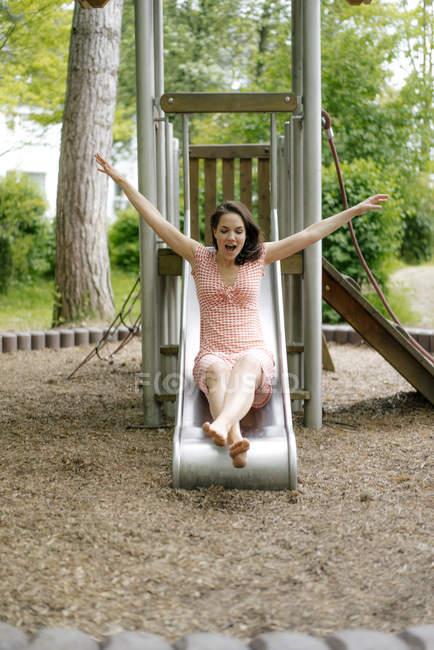Frau rutscht auf Spielplatz auf Rutsche — Stockfoto