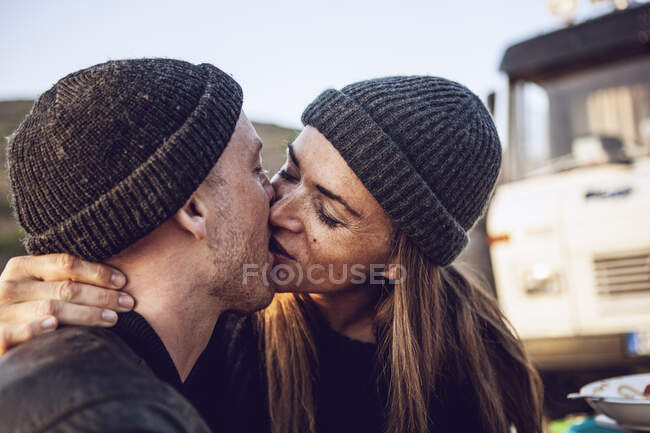 Kissing couple wearing wooly hats — Stock Photo
