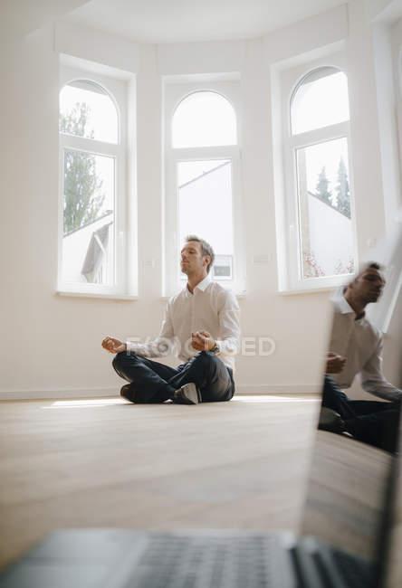 Geschäftsmann in frisch renoviertem Haus, im Schneidersitz auf dem Boden sitzend, meditierend, mit Laptop im Vordergrund — Stockfoto