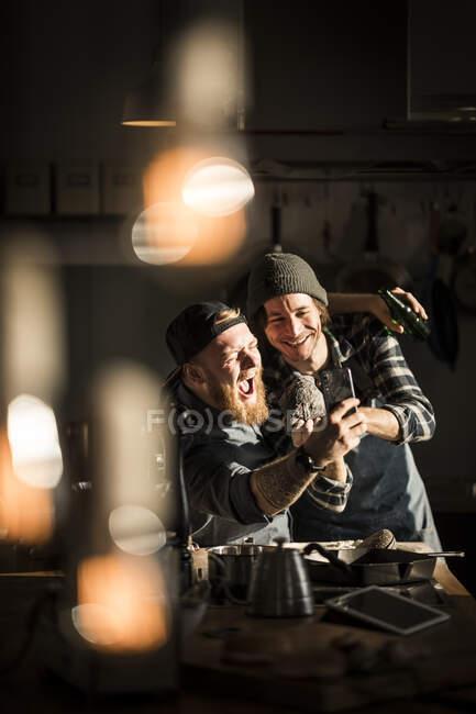 Молодой человек фотографировал своего друга, готовил на кухне — стоковое фото