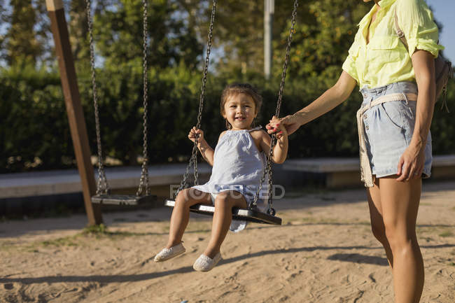 Mother holding daughter's hand swinging on a playground — Stock Photo