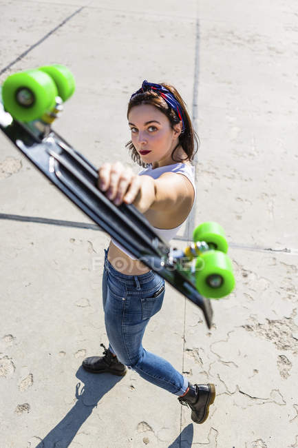 Portrait of young woman standing holding up skateboard — Stock Photo