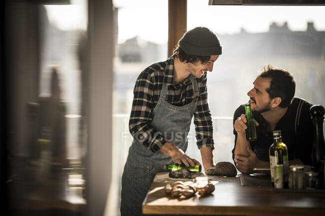 Friends cooking an d drinking beer in the kitchen — Stock Photo