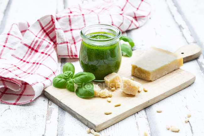 Glass of homemade pesto Genovese, ingredients and kitchen towel — Stock Photo