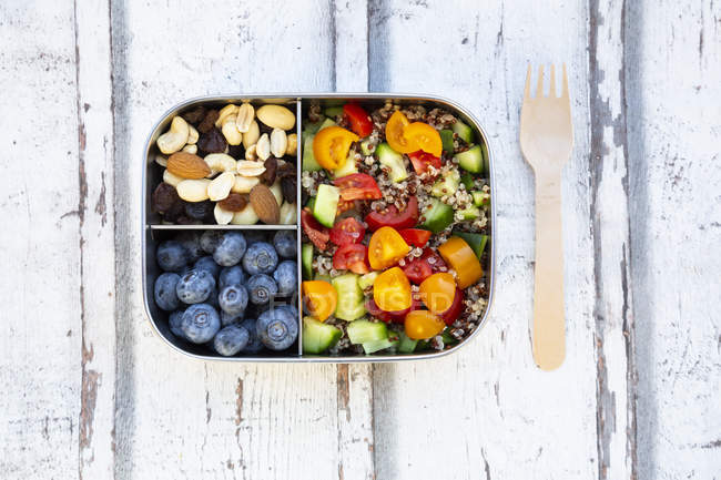 Lunchbox with quinoa salad with tomato and cucumber, blue berry and trail mix — Stock Photo
