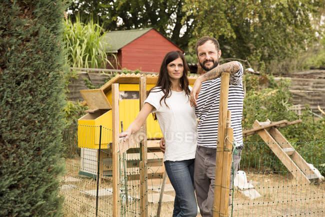 Портрет уверенной в себе пары, стоящей у курятника в саду — стоковое фото