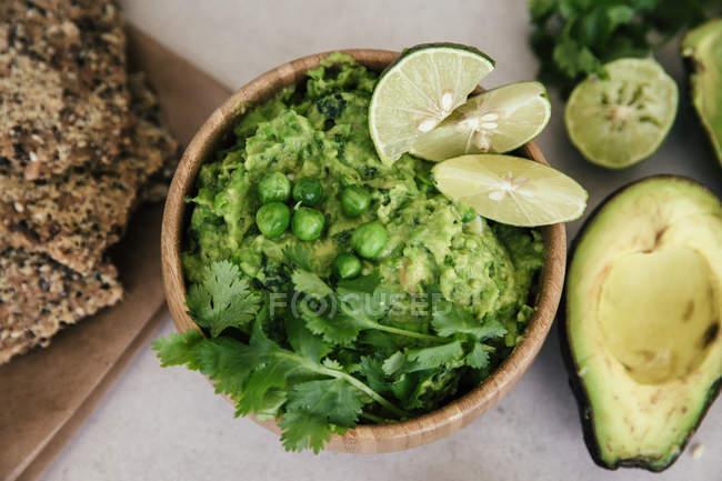 Ґуакомоль з горохом, авокадо, лаймом, кориандром і хрустким хлібом — стокове фото