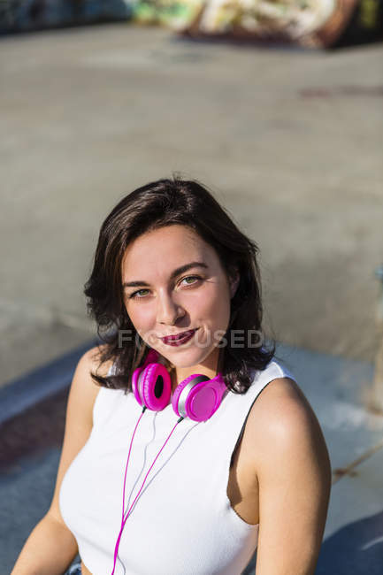 Portrait of smiling young woman with headphones in the city — Stock Photo