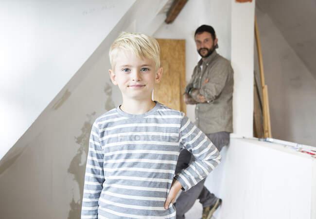 Портрет упевненого хлопця, який працює з батьком над перетворенням на горище — стокове фото