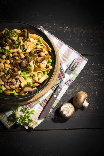 Ribbon noodles with Crimini Mushrooms, peas and chickpeas — стоковое фото
