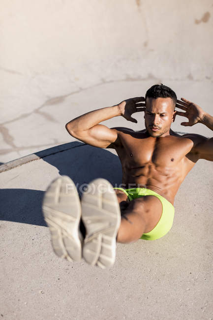 Barechested muscular man doing sit-ups in a skatepark — Stock Photo