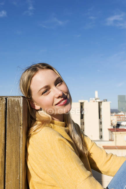 Молода жінка відпочиває на міському даху тераси. — стокове фото