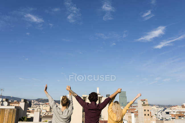 Friends having fun on an urban rooftop terrace, raising arms — Photo de stock