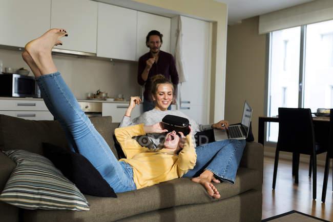 Amici seduti sul divano in salotto, giocando con gli occhiali VR — Foto stock
