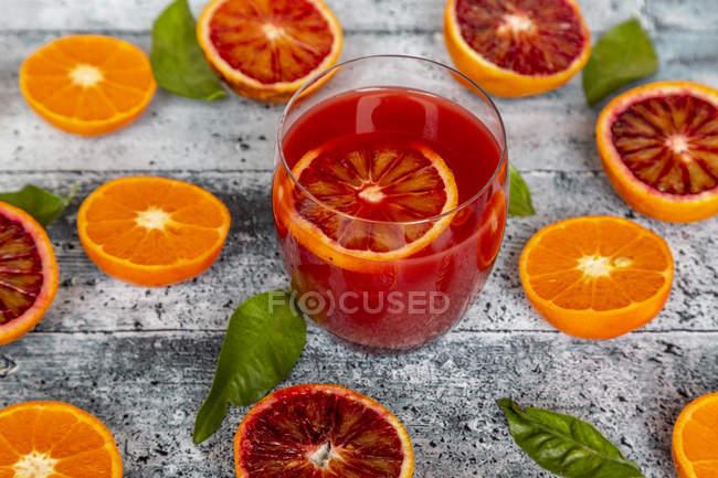 Copo de suco de laranja de sangue e metades de laranjas de sangue e tangerinas — Fotografia de Stock