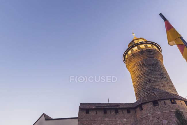 Deutschland, Nürnberg, Nürnberger Schloss, Sinwell Tower und Deutsche Flagge bei blauer Stunde, Flachwinkelansicht — Stockfoto