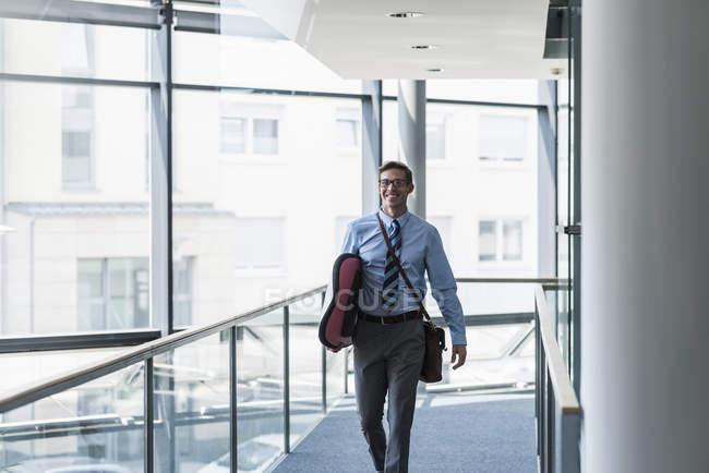 Homme d'affaires heureux portant planche de surf dans le bureau — Photo de stock