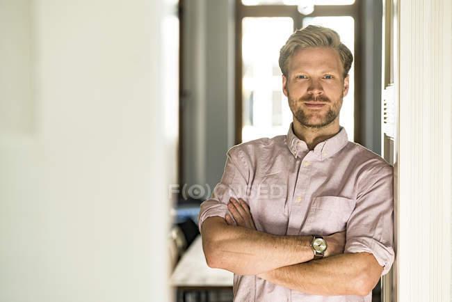 Portrait de l'homme confiant occasionnel appuyé contre le cas de porte à la maison — Photo de stock