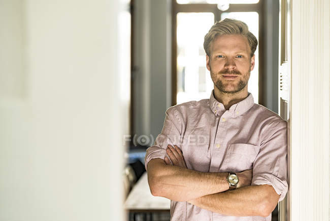 Портрет упевненого легковажного чоловіка, який стоїть проти домашньої справи. — стокове фото