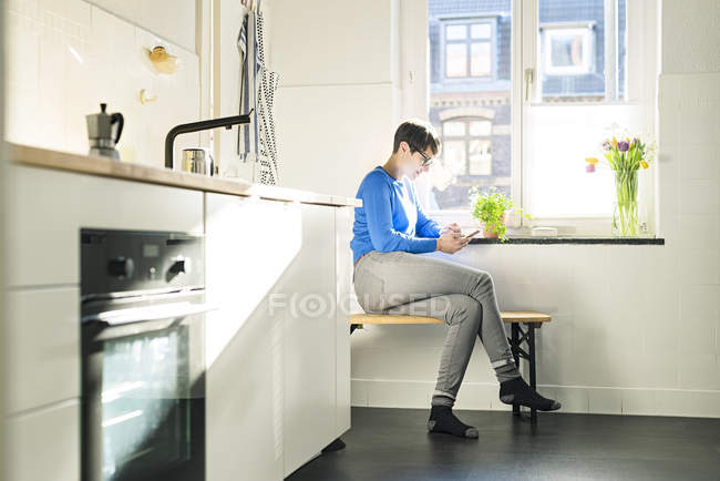 Short-haired woman sitting on bench in kitchen at the window using smartphone — Stock Photo