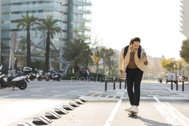 Человек смотрит на мобильный телефон во время скейтбординга в городе — стоковое фото