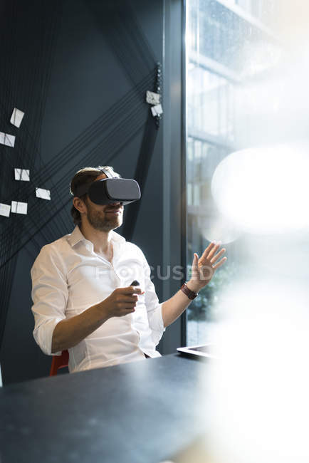 Business man with virtual reality glasses and tablet sitting in modern office — Stock Photo
