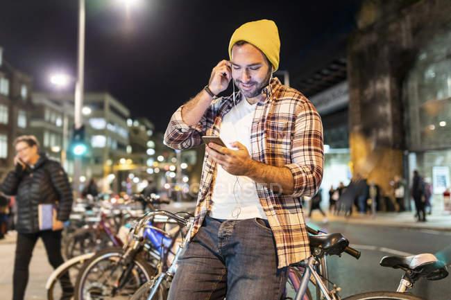 Reino Unido, Londres, hombre viajando de noche en la ciudad y mirando su teléfono - foto de stock