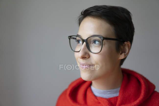 Portrait d'une jeune femme souriante aux cheveux courts, portant des lunettes — Photo de stock