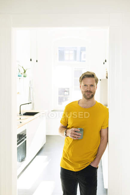 Confident casual man with coffee mug leaning against door case — Stock Photo