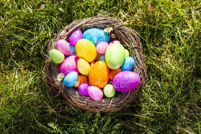 Ovos de Easter coloridos em um ninho na grama — Fotografia de Stock