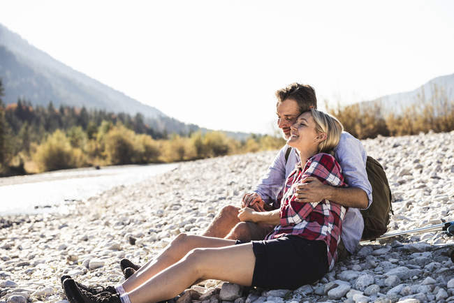 Austria, Alps, happy couple on a hiking trip having a break at a brook — Stock Photo
