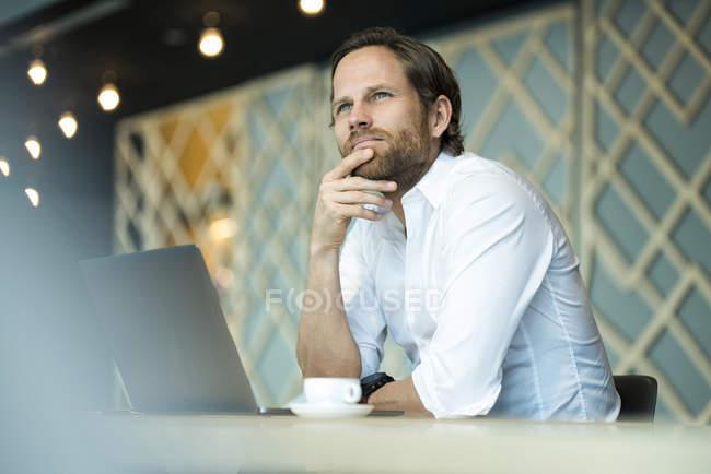 Случайный пенсионный предприниматель, работающий на ноутбуке в офисном зале — стоковое фото