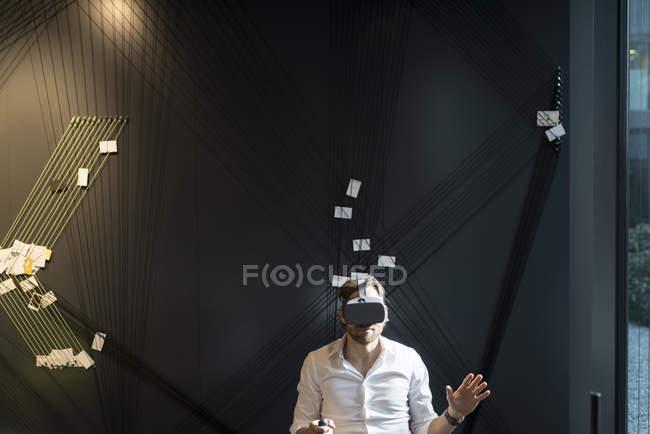 Деловой человек в очках виртуальной реальности и планшете сидит в современном офисе — стоковое фото