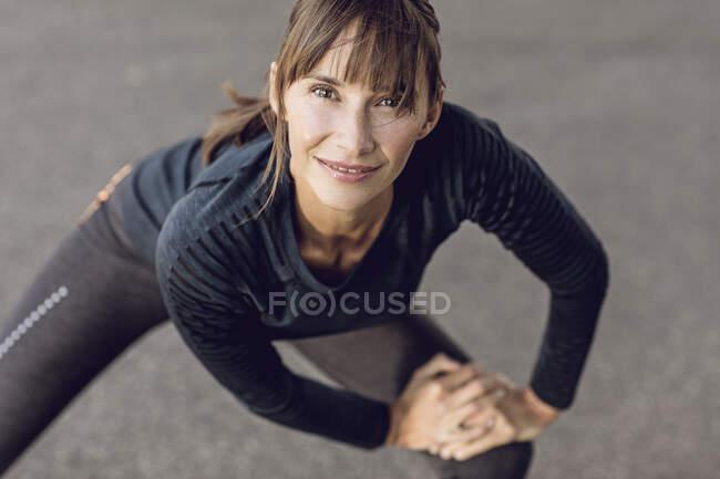 Спортивна жінка тренується на свіжому повітрі, розтягуючись — стокове фото