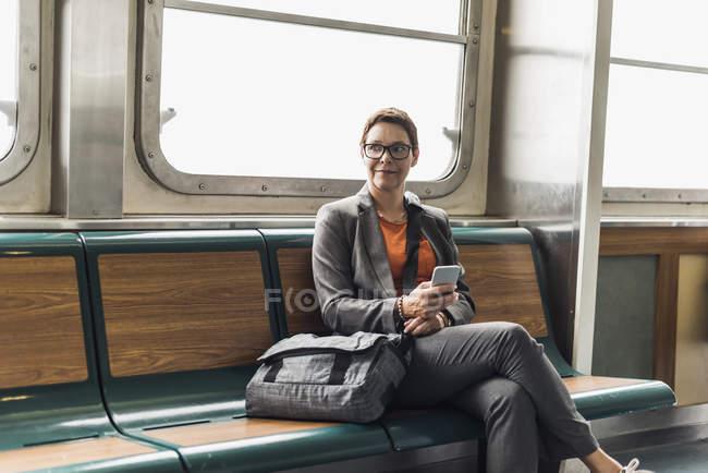 Femme d'affaires tenant un téléphone portable sur un ferry — Photo de stock
