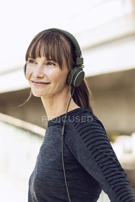 Mujeres deportivas con audífonos, haciendo su entrenamiento de fitness al aire libre. - foto de stock