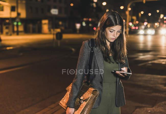 Молодая деловая женщина с кожаной сумкой смотрит на мобильный телефон ночью — стоковое фото