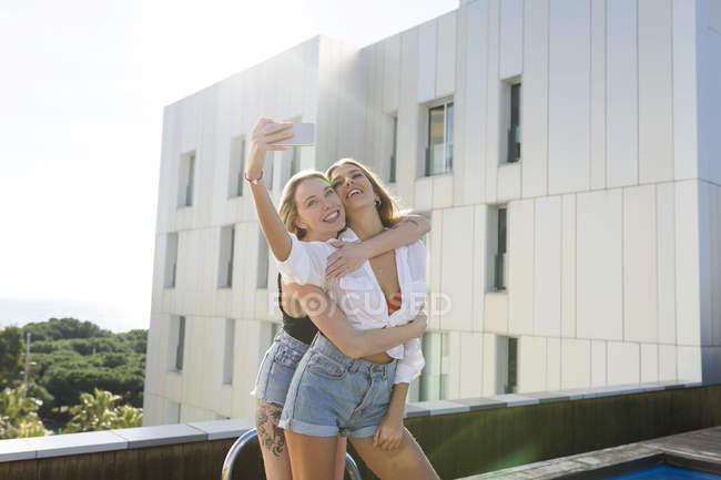 Girlfriends on a rooftop terrace, having fun by the pool, taking selfies — Fotografia de Stock