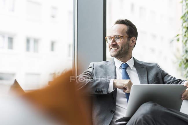 Бизнесмен, сидящий в холле с ноутбуком — стоковое фото