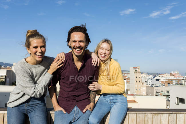 Friends sitting on an urban rooftop terrace, with arms around — Stock Photo