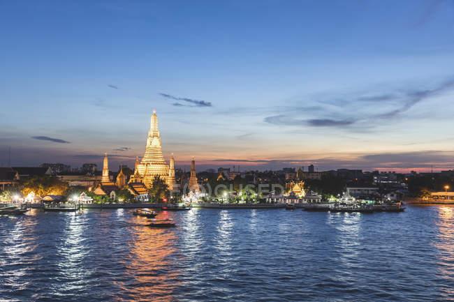 Thailand, Bangkok, Wat Arun temple at dusk with Chao Phraya river on foreground — Stock Photo