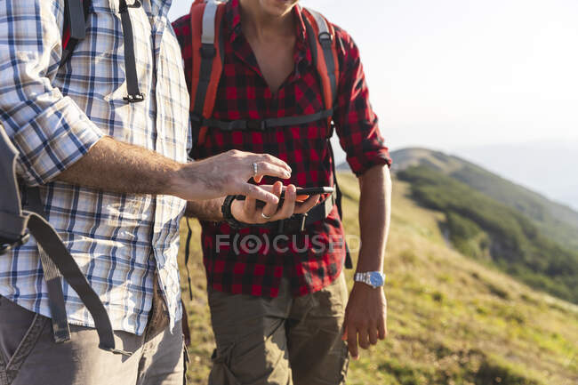 Italy, Monte Nerone, close-up of two men hiking and using smartphone in mountains — Stock Photo