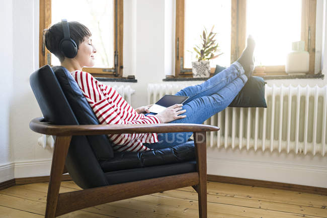 Short-haired woman with headphones relaxing in lounge chair in stylish apartment — Stock Photo