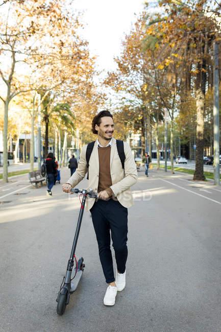 Homme souriant avec sac à dos E-Scooter en ville — Photo de stock