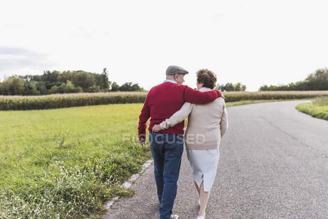 Старша пара гуляє по сільській місцевості. — стокове фото