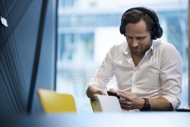 Homem de negócios casual com fones de ouvido, trabalhando em smartphone no escritório moderno — Fotografia de Stock