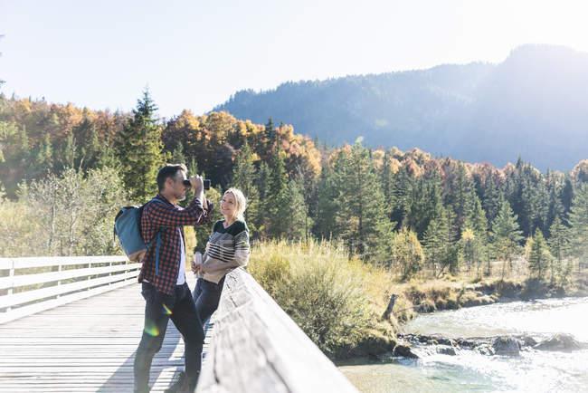 Austria, Alps, couple on a hiking trip with man looking through binoculars — Stock Photo