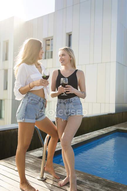 Girlfriends on a rooftop terrace, having fun by the pool, drinking red wine — Fotografia de Stock