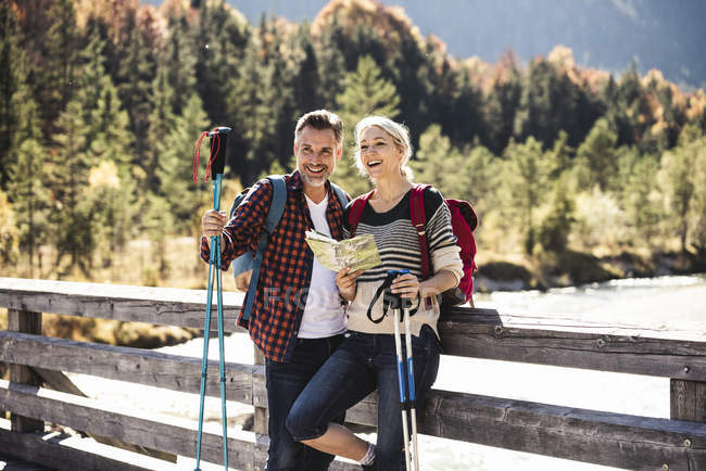Austria, Alps, happy couple on a hiking trip with map on a bridge — Stock Photo