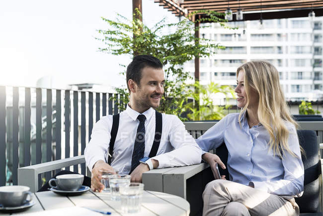 Smiling business colleagues on city terrace having a break and talking with each other — Stock Photo